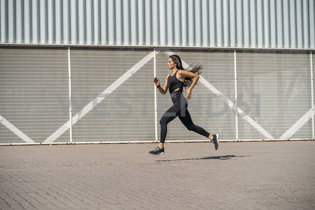Young female jogger running in front of a wall - MTBF00034 - Mikel Taboada/Westend61