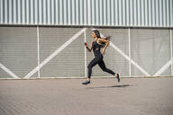 Young female jogger running in front of a wall - MTBF00034