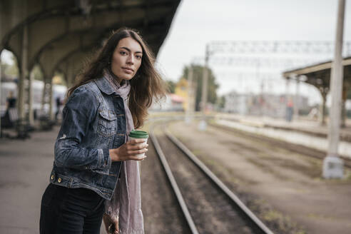Young female traveller with coffee to go on train station - VPIF01740