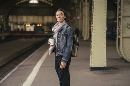Young female traveller with coffee to go on the platform - VPIF01746