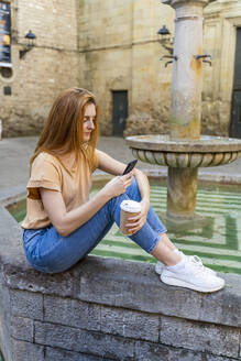 Woman using smartphone sitting on a fountain - AFVF04150