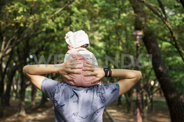 Father walking in a park with baby girl on his shoulders - GEMF03233 - Gemma Ferrando/Westend61
