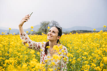 Portrait of happy woman taking selfie with smartphone in a rape field, Gyeongju, South Korea - GEMF03236