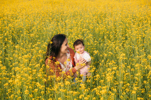 Happy mother with baby girl in a rape field - GEMF03239