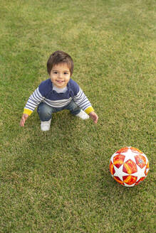 Portrait of smiling little boy with a ball crouching on lawn - VGF00316