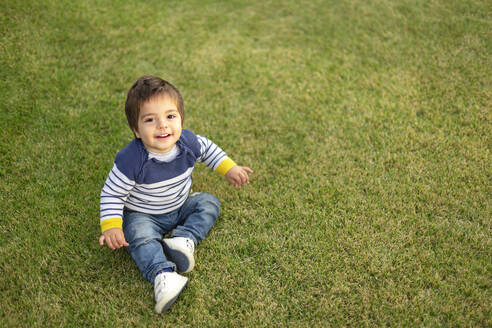 Portrait of smiling little boy sitting on lawn - VGF00319