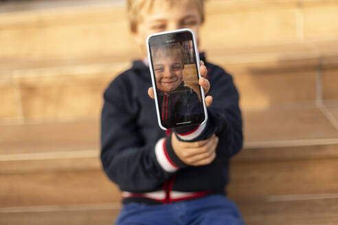 Display of mobile phone showing smiling little boy, close-up - VGF00325