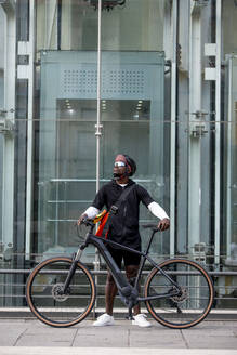 Stylish young man with bicycle and messenger bag in the city - CJMF00151