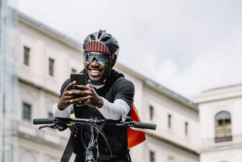 Happy stylish young man with bicycle, smartphone and messenger bag in the city - CJMF00160