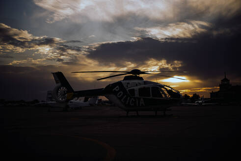 Spain, Madrid, Silhouette of police helicopter in helipad at dawn - OCMF00824