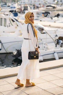 Young muslim woman wearing yellow hijab walking at the harbour - MPPF00213