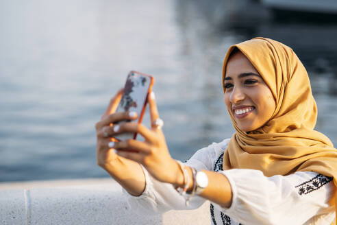 Young muslim woman wearing yellow hijab and using smartphone and taking a selfie - MPPF00219