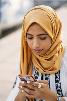 Young muslim woman wearing yellow hijab and using smartphone - MPPF00222