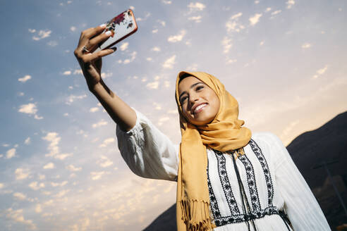 Young muslim woman wearing yellow hijab and using smartphone and taking a selfie in the evening - MPPF00237