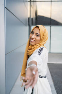 Young muslim woman smiling, wearing yellow hijab and giving her hand - MPPF00240