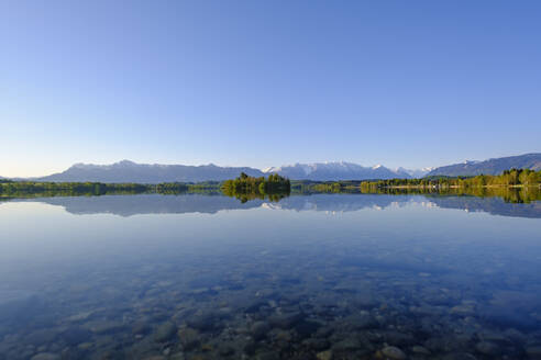 Germany, Bavaria, Uffing am Staffelsee, Scenic view of Staffelsee lake reflecting clear sky and surrounding mountains - SIEF09202