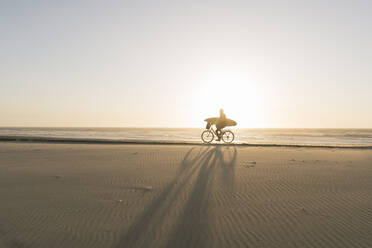Surfer riding a bicycle during the sunset in the beach, Costa Nova, Portugal - AHSF01043