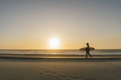 Surfer walking with the surfboard during the sunset at the beach - AHSF01046