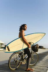 Surfer riding a bicycle during the sunset, holding surf board - AHSF01055