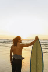 Surfer standing at the beach at sunset - AHSF01061
