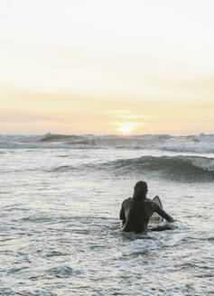 Rear view of surfer with surfboard sitting on surfboard in the ocean during the sunset - AHSF01064