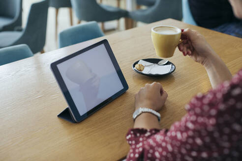 Woman having coffee and looking at computer tablet - MOMF00790