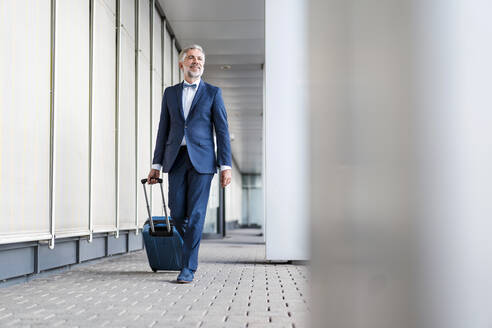Mature businessman in a passageway with rolling suitcase on the go - DIGF08514