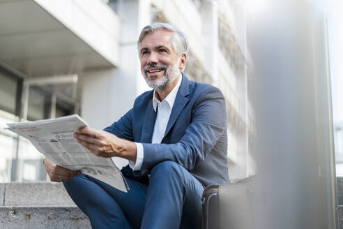 Smiling mature businessman sitting on stairs in the city with newspaper - DIGF08532
