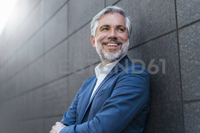Portrait of smiling mature businessman at a wall - DIGF08547 - Daniel Ingold/Westend61