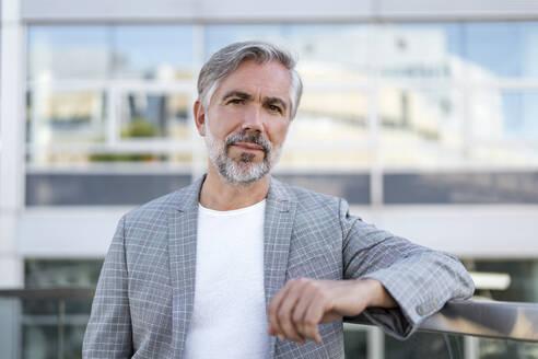Portrait of fashionable mature businessman outdoors - DIGF08559