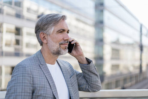Portrait of mature businessman on the phone - DIGF08565