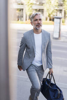 Fashionable mature businessman with travelling bag on the go in the city - DIGF08568