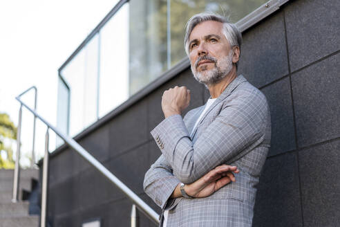 Fashionable mature businessman standing on stairs - DIGF08574