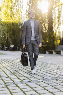 Fashionable mature businessman with bag on the go in the city - DIGF08604