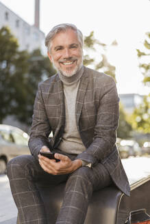 Portrait of smiling fashionable mature businessman in the city - DIGF08607