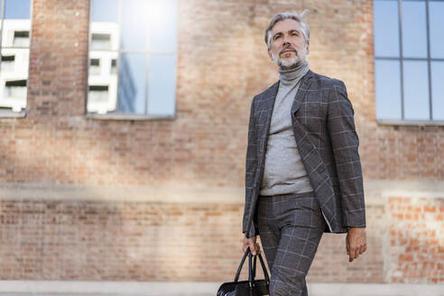 Fashionable mature businessman with bag on the go in the city - DIGF08610