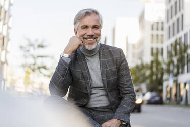 Portrait of smiling fashionable mature businessman in the city - DIGF08622