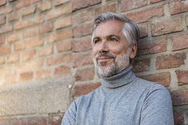 Portrait of mature businessman at a brick wall - DIGF08628