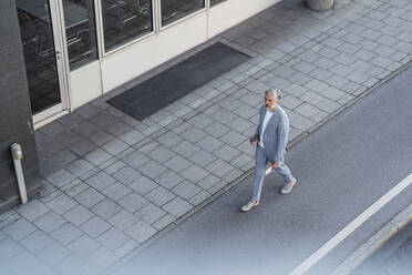 Top view of mature businessman walking on a road - DIGF08634
