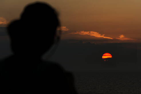 Silhouette of woman looking at sunset - JOHF04465