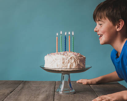 Boy ready to blow out candles on birthday cake on blue background. - CAVF65894