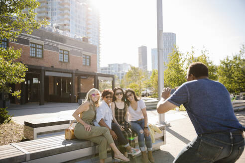 Man with camera phone photographing mature women friends on sunny city bench - HEROF39601