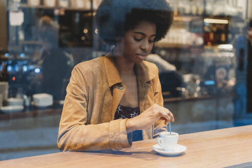 Young woman with afro hair having coffee in cafe - CUF52564