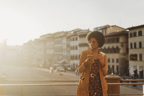 Young woman with afro hair having hot drink, using smartphone in city, Florence, Toscana, Italy - CUF52567