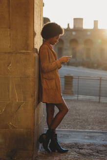 Young woman with afro hair using smartphone, leaning against stone wall, Florence, Toscana, Italy - CUF52570