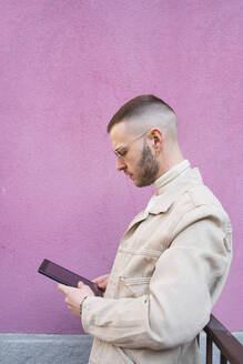 Young man using digital tablet, pink background - CUF52741