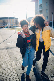 Two cool young female friends laughing on urban sidewalk - CUF52777