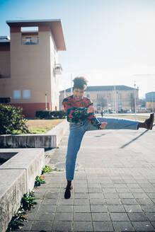 Young woman jumping and kicking leg on urban sidewalk, full length portrait - CUF52792