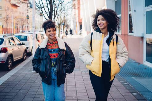Two cool young women strolling on urban sidewalk - CUF52810