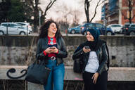 Young woman in hijab and her friend using smartphones and laughing by city canal - CUF52846